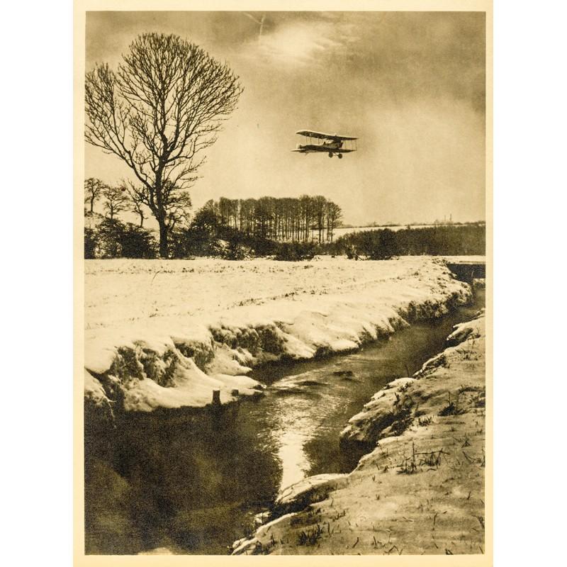 Doppeldecker über einer Winterlandschaft. Original-Fotografie - Silbergelatine-Abzug, braun getont (ca. 1920).